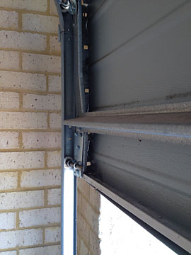 Sectional garage door bottom panel vehicle impact damage